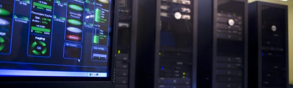 Close-up of a computer monitor in front of network servers